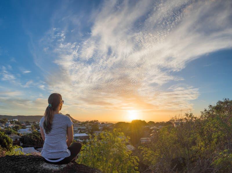 Jonge vrouw die op Hawaiiaanse zonsondergang letten stock fotografie