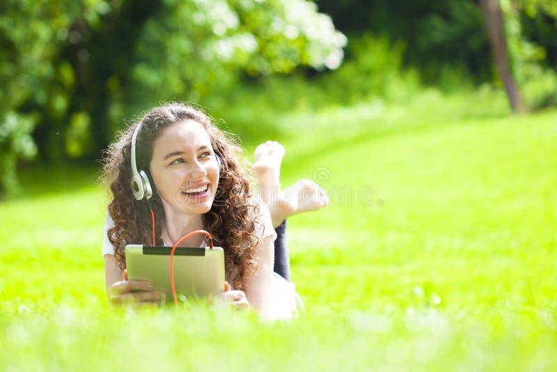 Jonge vrouw die op het gras liggen die aan muziek luisteren royalty-vrije stock afbeeldingen