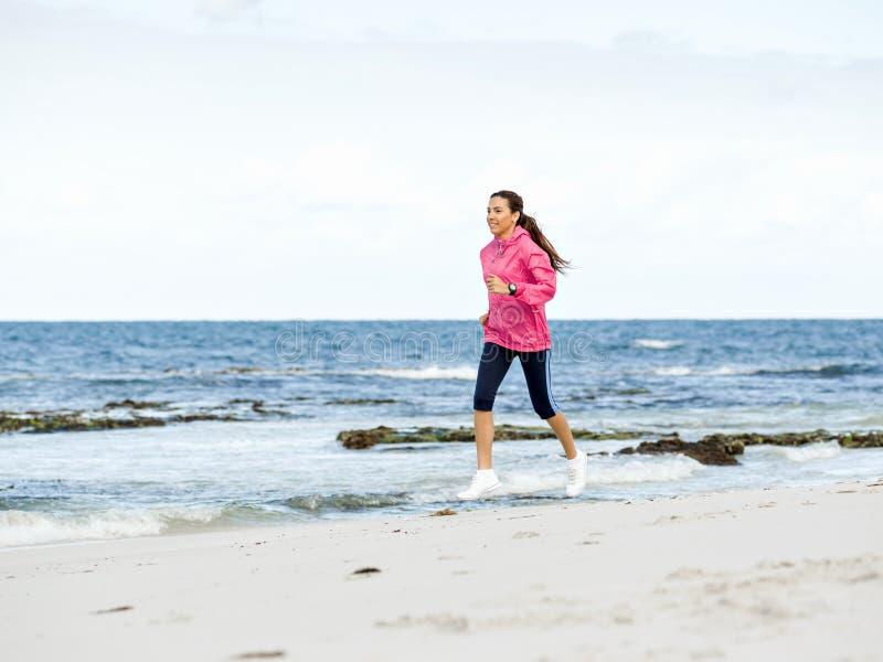 Jonge vrouw die op het strand aanstoot royalty-vrije stock fotografie
