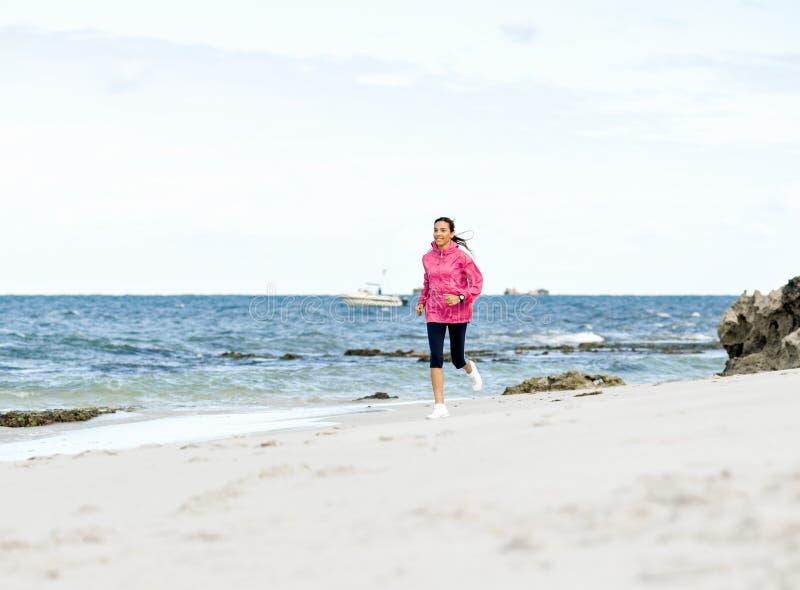 Jonge vrouw die op het strand aanstoot royalty-vrije stock afbeelding