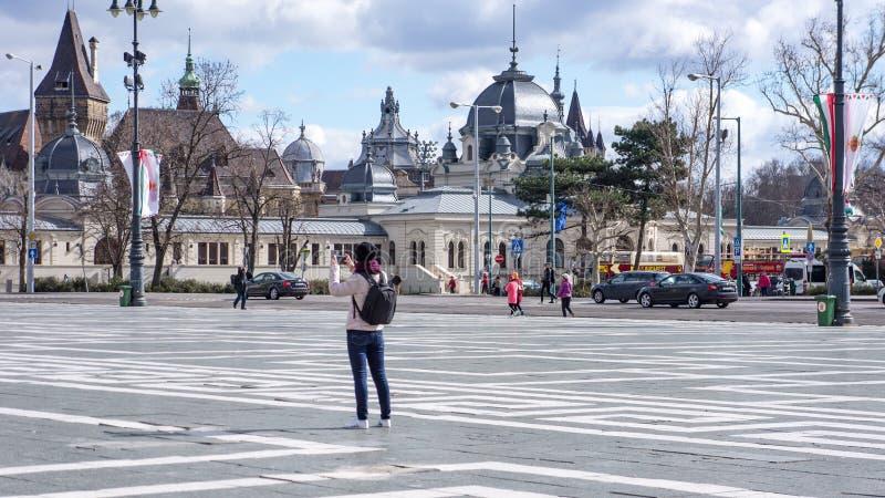 Jonge vrouw die op het Vierkant van Helden in Boedapest Hongarije fotograferen stock fotografie