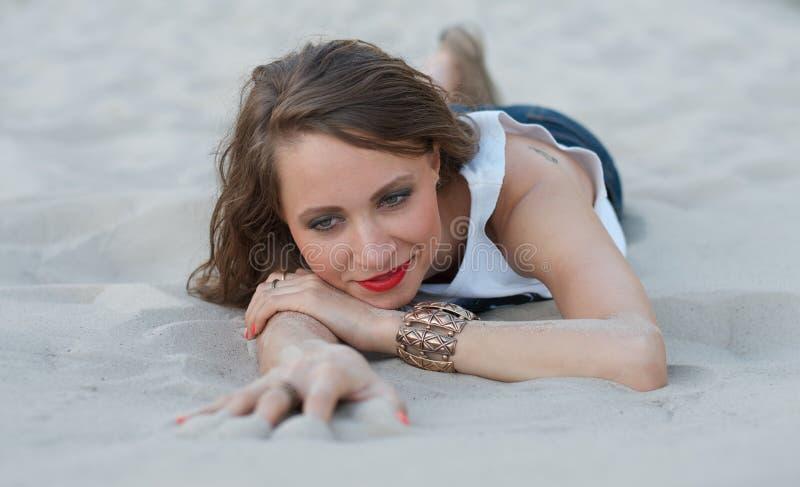 Jonge vrouw die op het zand ligt stock fotografie
