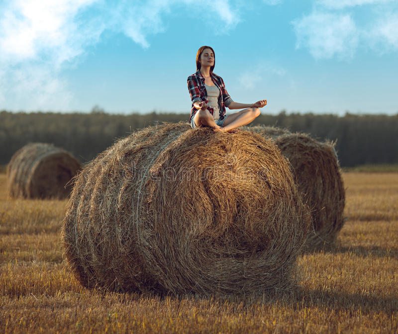 Jonge vrouw die op hooiberg mediteren royalty-vrije stock foto