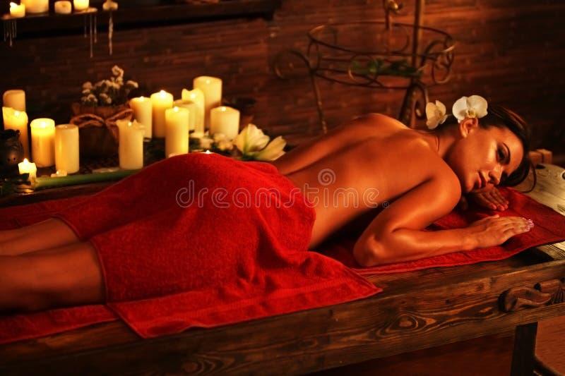 Jonge vrouw die op houten kuuroordbed in massage spa salon liggen royalty-vrije stock foto