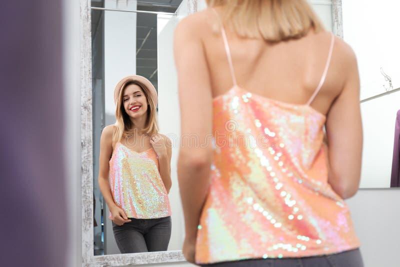 Jonge vrouw die op kleren in kleedkamer proberen royalty-vrije stock foto's