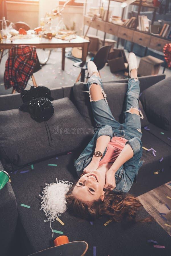 Jonge vrouw die op laag liggen en omhoog in slordige ruimte na partij kijken stock foto