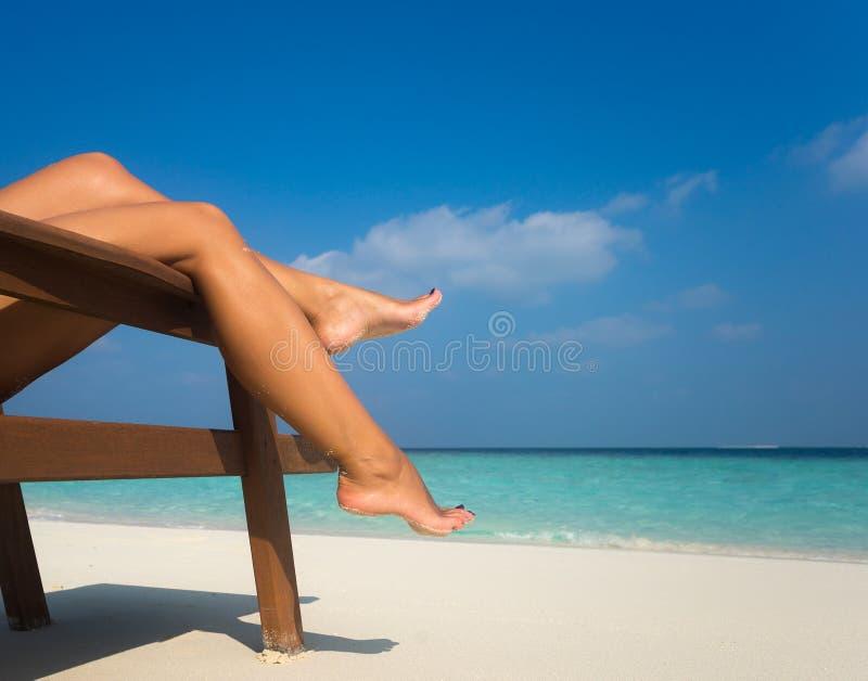 Jonge vrouw die op lanterfanter zonnebaden benen stock foto