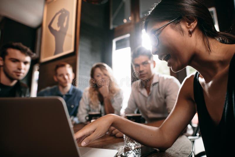 Jonge vrouw die op laptop richten en met vrienden bespreken royalty-vrije stock afbeelding
