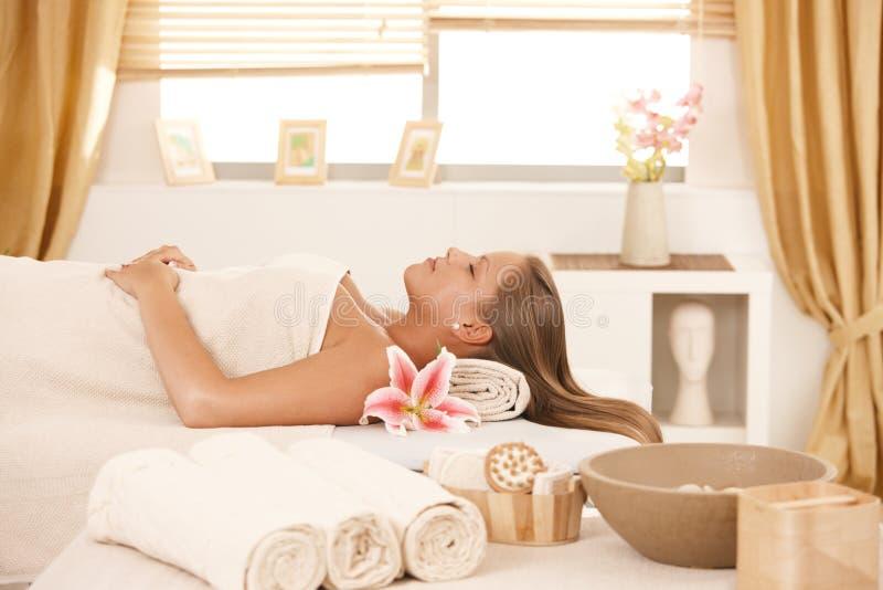 Jonge vrouw die op massagebed bij kuuroord rust. stock foto