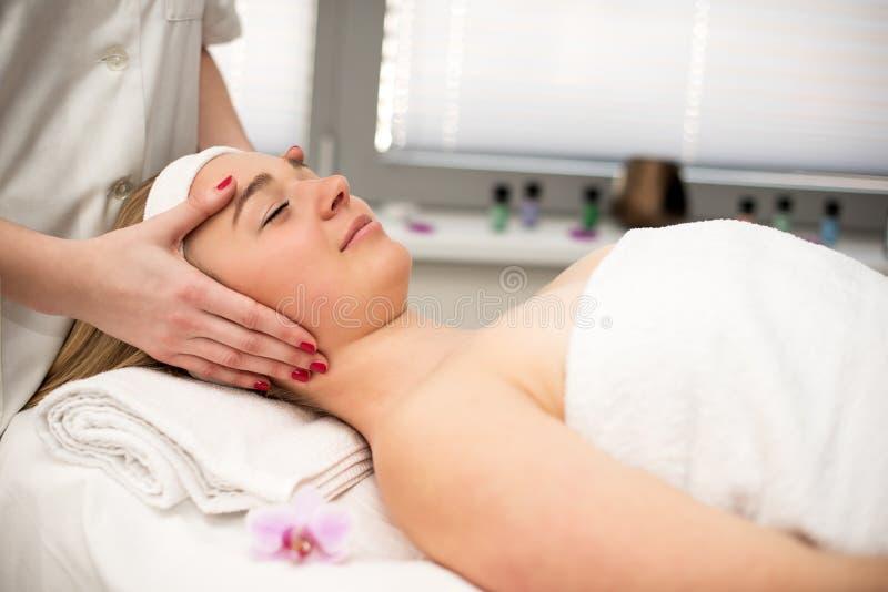 Jonge vrouw die op massagelijst liggen die gezichtsmassage ontvangen beaut stock afbeeldingen