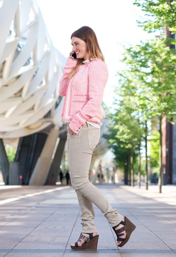Jonge vrouw die op mobiele telefoon in de stad spreken stock foto's