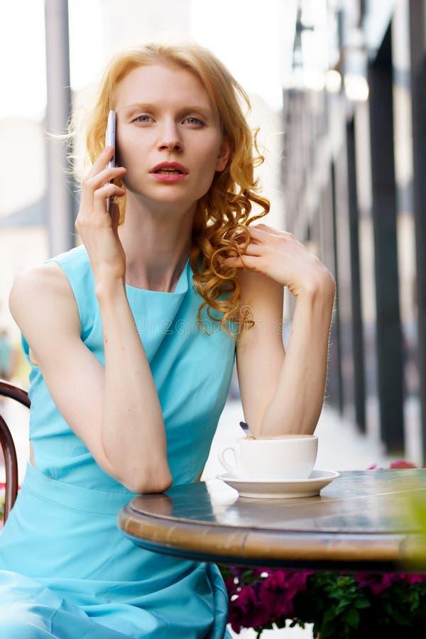 Jonge vrouw die op mobiele telefoon in een koffie spreken stock fotografie