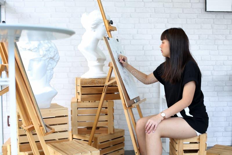 Jonge vrouw die op schildersezel schetsen stock foto's