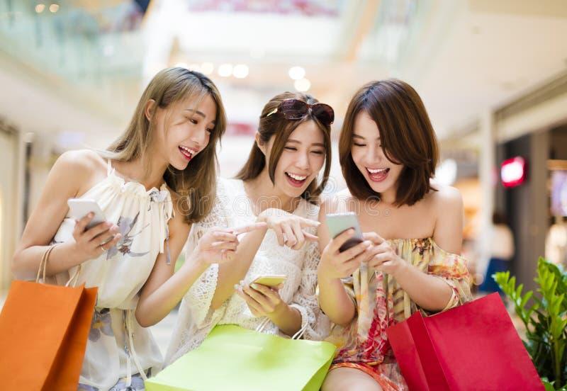 jonge vrouw die op slimme telefoon in winkelcomplex letten stock afbeelding
