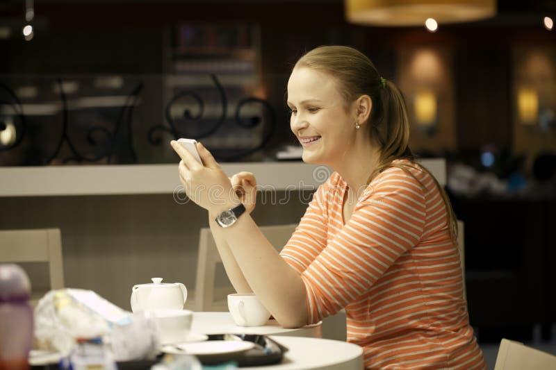 Jonge vrouw die op smartphone in koffie babbelen. stock afbeeldingen