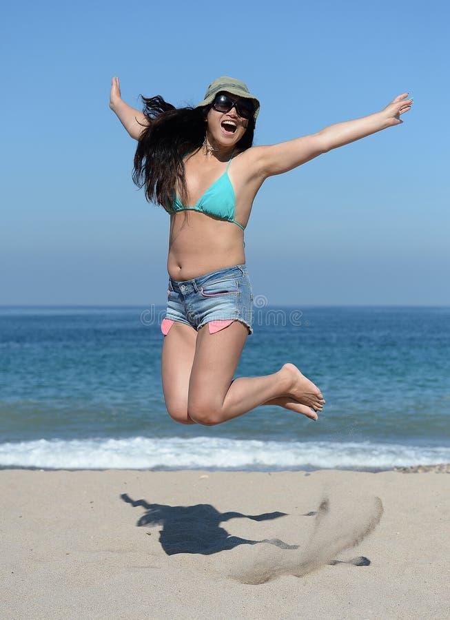 Jonge vrouw die op strand springt stock afbeelding