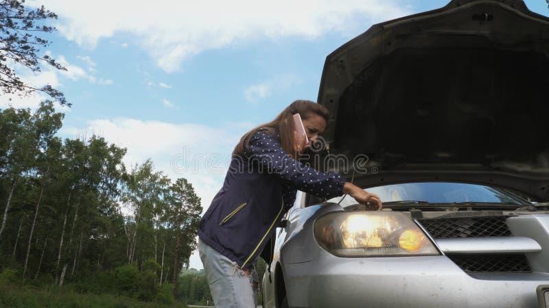 Jonge vrouw die op telefoon dichtbij de kap van een gebroken auto spreken stock foto