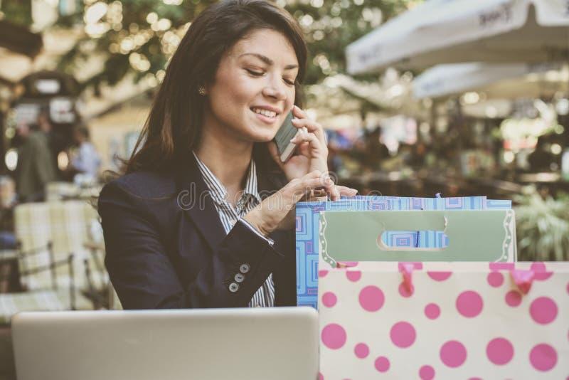 Jonge vrouw die op telefoon spreken, die bij koffie na het winkelen zitten stock afbeeldingen