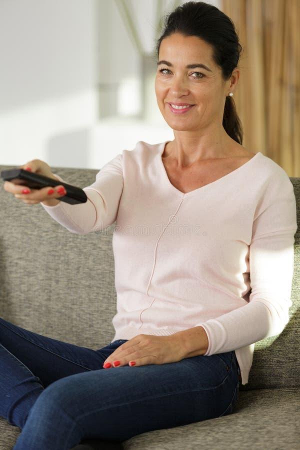 Jonge vrouw die op TV op bank letten stock foto