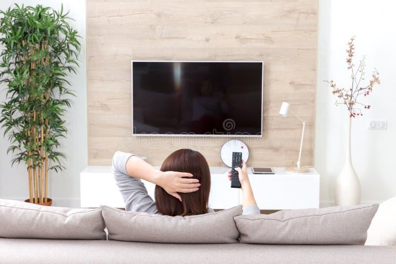 Jonge vrouw die op TV in de ruimte letten stock afbeelding