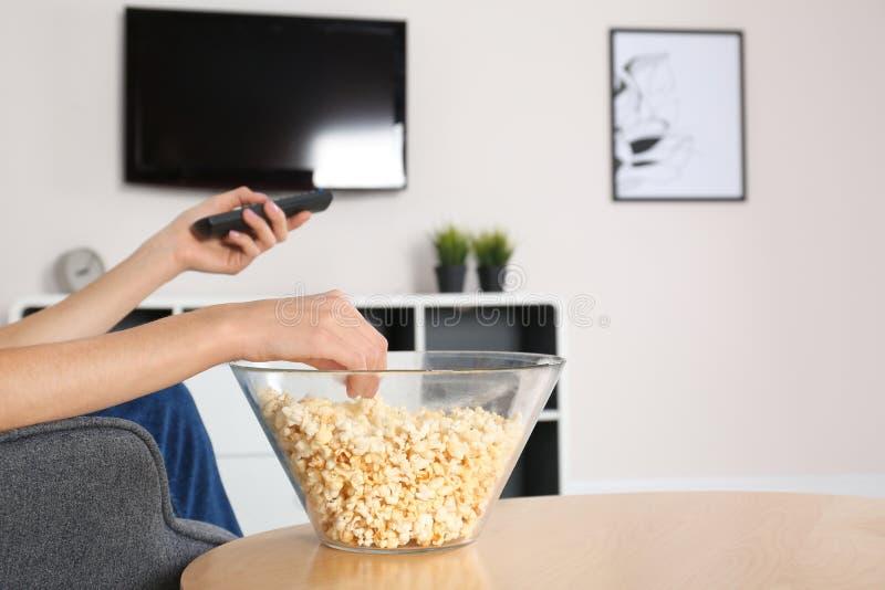 Jonge vrouw die op TV letten terwijl het eten van popcorn royalty-vrije stock foto