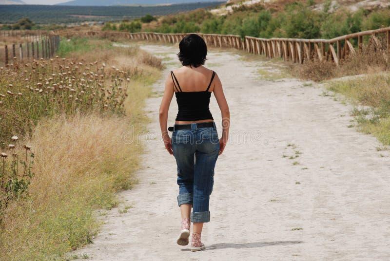 Jonge vrouw die op weg op het gebied loopt royalty-vrije stock afbeeldingen