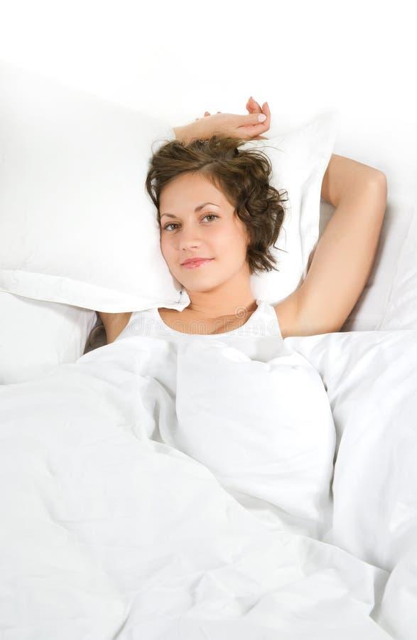 Jonge vrouw die op wit die bedlinnen liggen, op witte backgrou wordt geïsoleerd royalty-vrije stock foto
