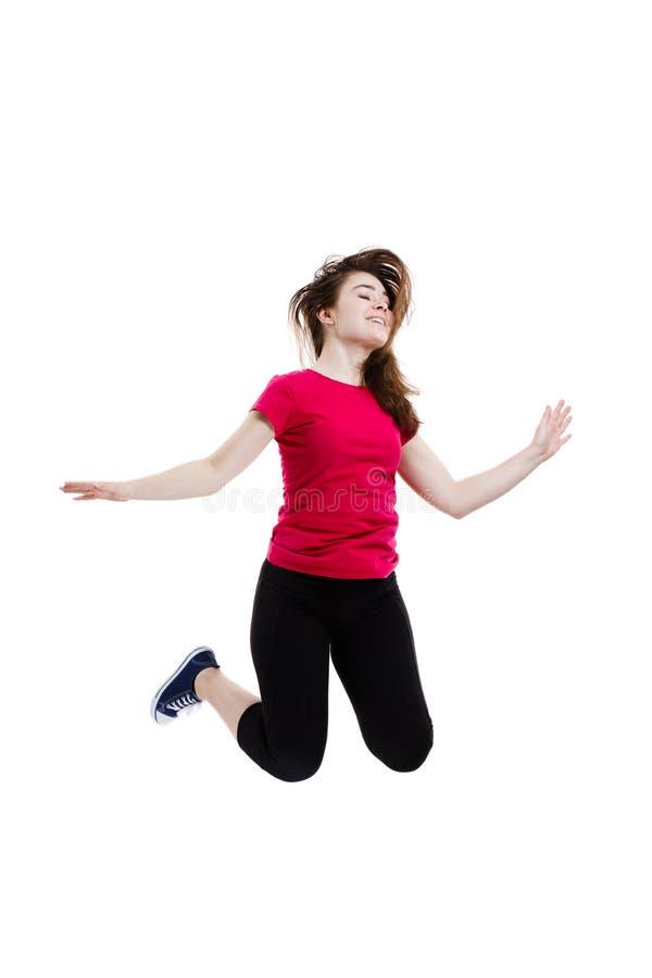 Jonge vrouw die op witte achtergrond springen stock foto's