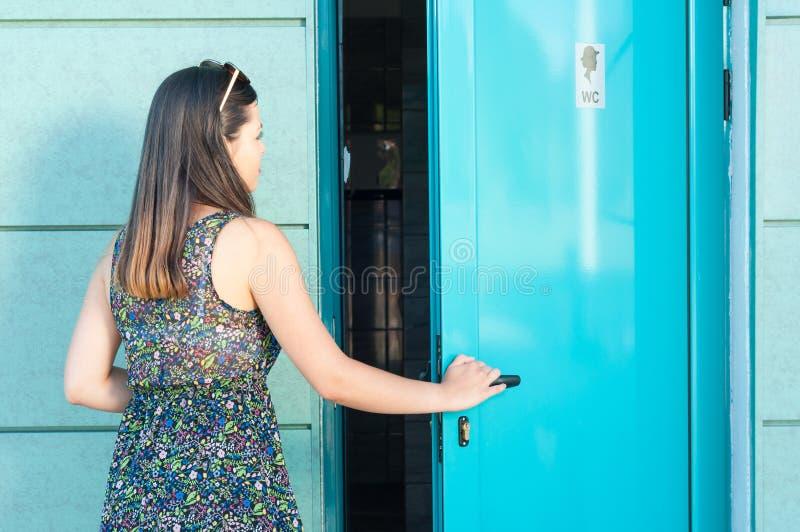 Jonge vrouw die openbaar toilet buiten in park ingaan stock foto