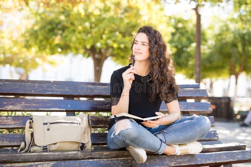 Jonge vrouw die in openlucht bestuderen royalty-vrije stock foto's