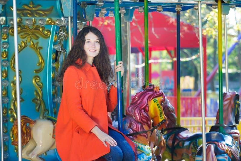Jonge vrouw die oranje horseback van de laagcarrousel openluchtportret dragen stock foto