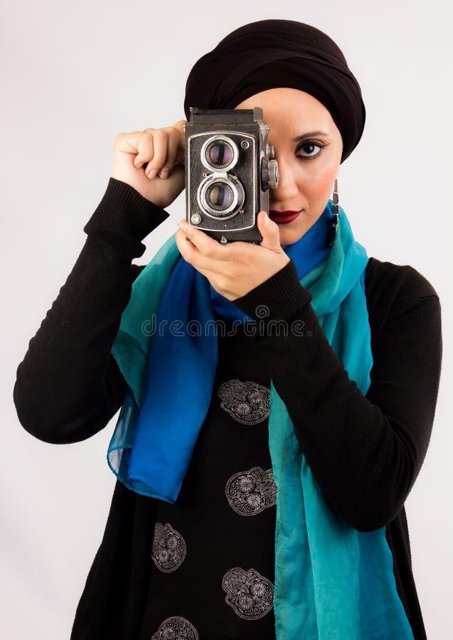 Jonge Vrouw die oude camera in hijab en kleurrijke sjaal houden stock foto's