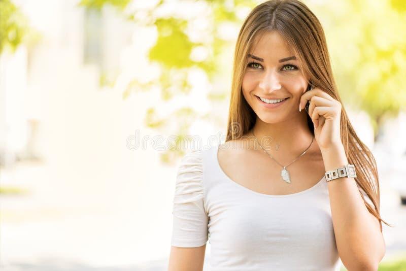 Jonge Vrouw die outoors van een Celtelefoon gebruiken royalty-vrije stock fotografie