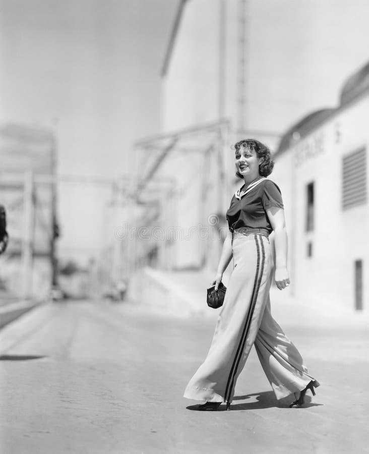 Jonge vrouw die over de weg lopen (Alle afgeschilderde personen leven niet langer en geen landgoed bestaat Leveranciersgaranties  royalty-vrije stock foto