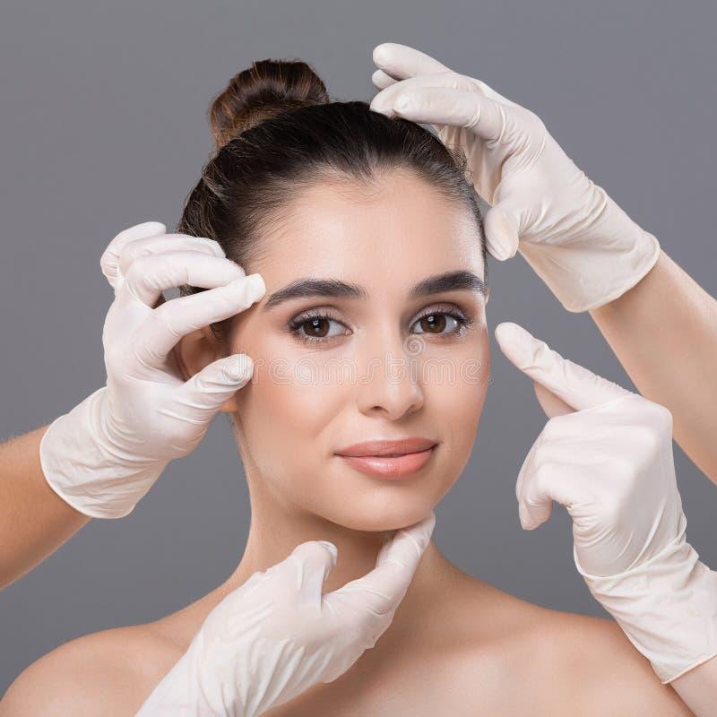 Jonge vrouw die overleg krijgen bij plastische chirurgiekliniek stock afbeeldingen