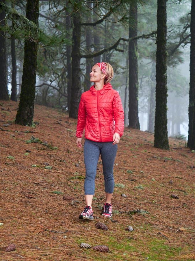 Jonge vrouw die overweldigend de herfst mistig bos onderzoeken royalty-vrije stock fotografie