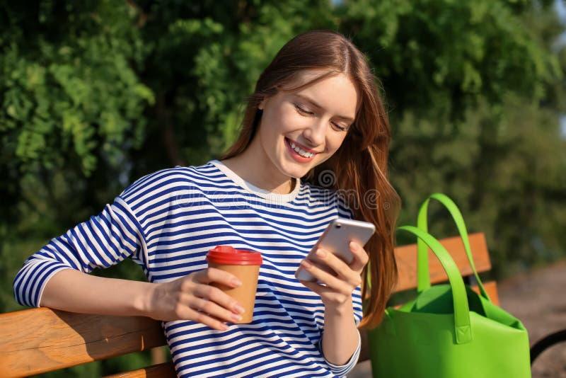 Jonge vrouw die in park op zonnige dag rusten stock afbeeldingen