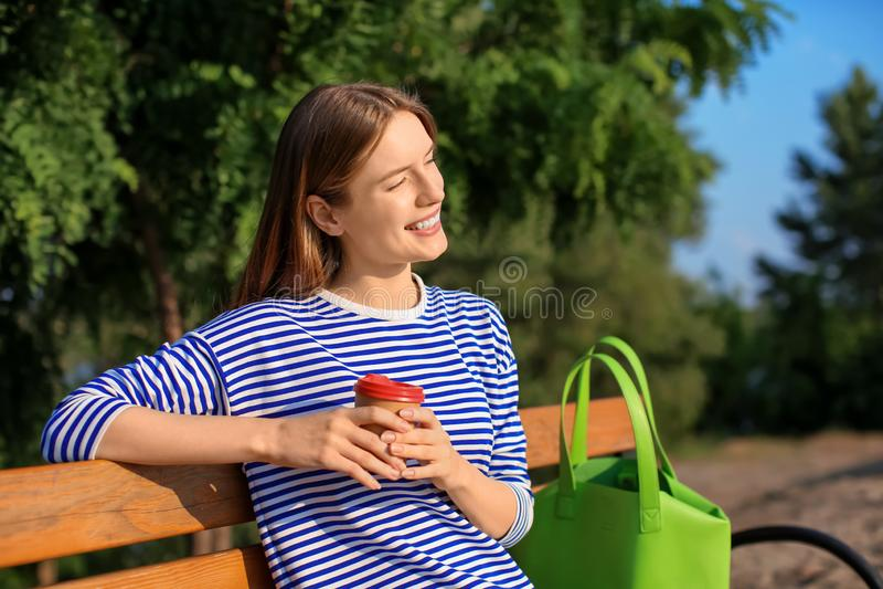 Jonge vrouw die in park op zonnige dag rusten royalty-vrije stock afbeeldingen