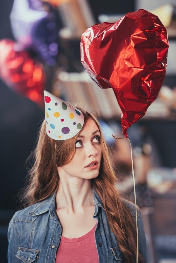 Jonge vrouw die in partijhoed ballon bekijken stock afbeeldingen