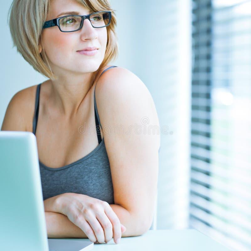 jonge vrouw die pensively uit het venster kijkt stock afbeelding