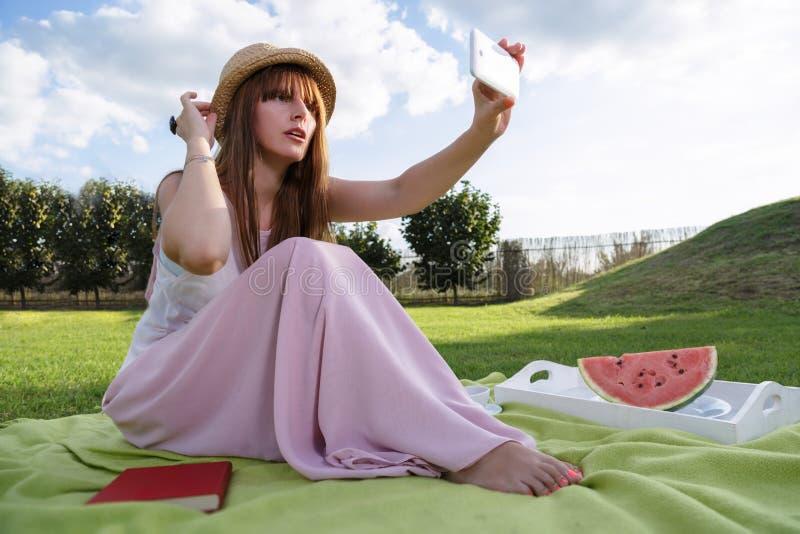 Jonge vrouw die picknic in park hebben royalty-vrije stock foto