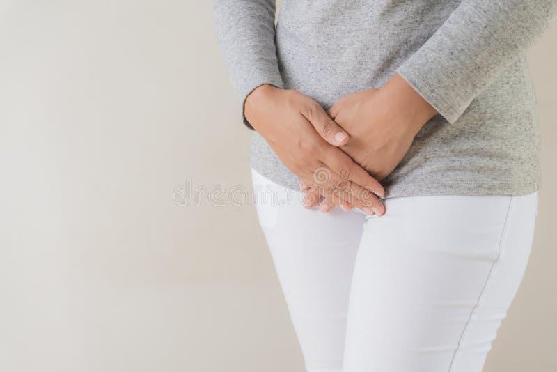 Jonge vrouw die pijnlijke maagpijn met handen hebben die lager het drukken van haar bifurcatiebuik houden royalty-vrije stock afbeelding