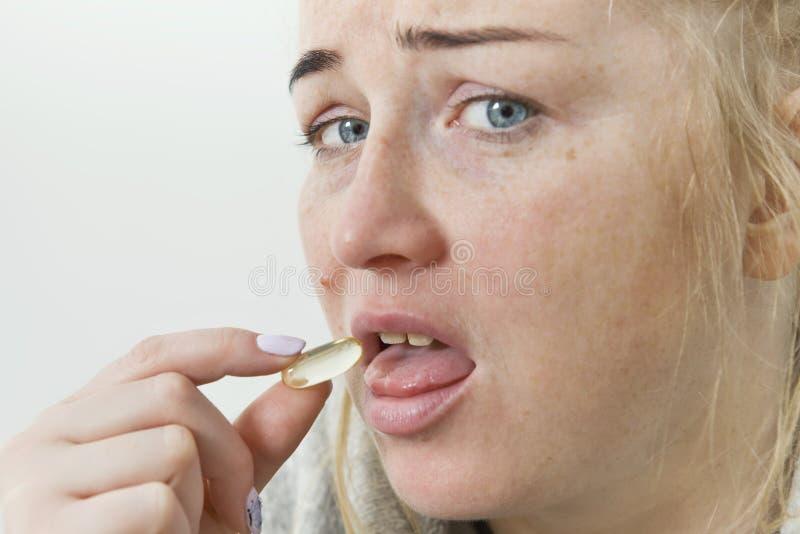 Jonge vrouw die pil of drug, gezondheids en geneeskundeconcepten nemen stock foto's