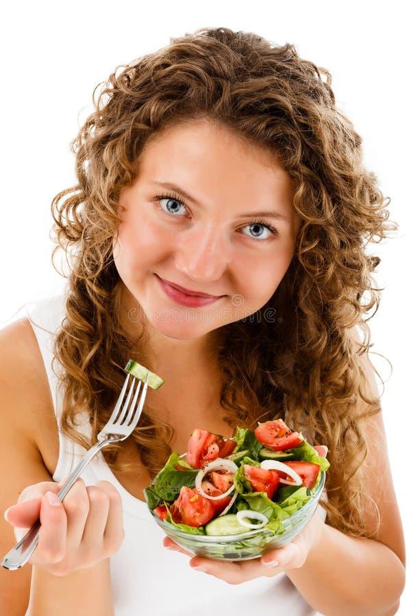 Jonge vrouw die plantaardige salade op witte achtergrond eten stock fotografie