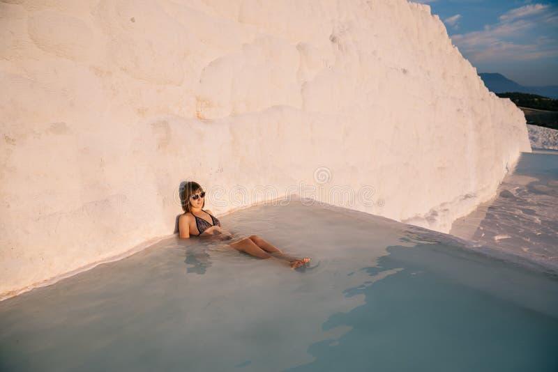 jonge vrouw die in pool dichtbij witte rots rusten stock afbeelding