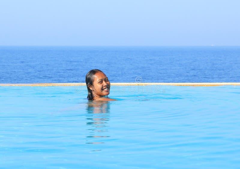Jonge vrouw die in pool door overzees zwemmen stock afbeeldingen