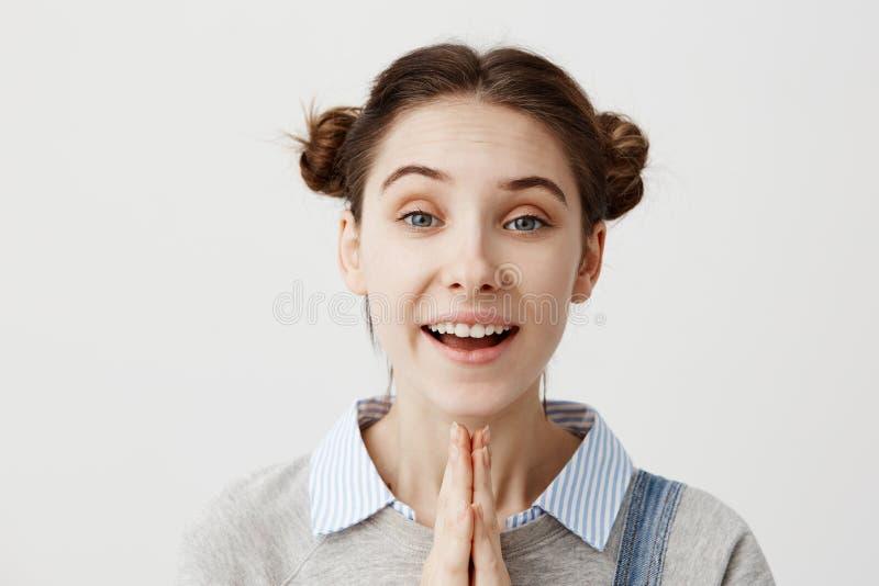 Jonge vrouw die positiveness en geluk uitdrukken die met palmen zich over witte achtergrond verenigen Spontaan brunette stock afbeeldingen