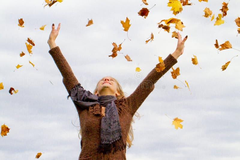 Jonge vrouw die pret in de herfst hebben stock afbeelding