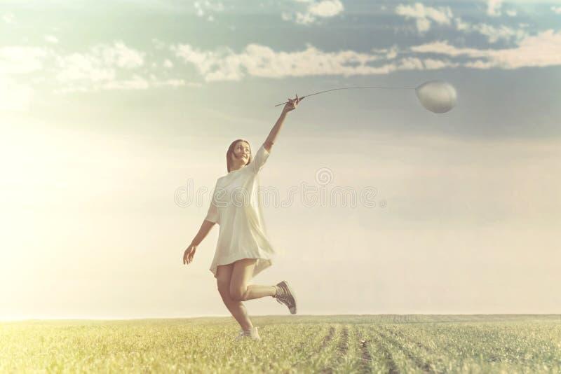 Jonge vrouw die pret met ballon in een groene weide hebben stock fotografie