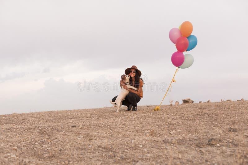 Jonge vrouw die pret met haar hond hebben in openlucht Hond die haar gezicht likt Heliumballons bovendien Zonsondergang Bewolkte  stock fotografie